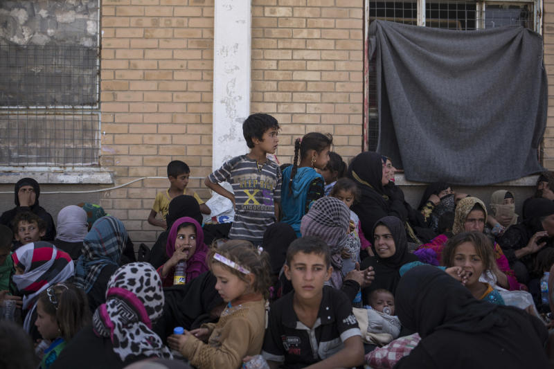 FILE - In this Tuesday, Oct. 3, 2017 file photo, women and children from Hawija sit outside a Kurdish screening center to determine if they were associated with the Islamic State group, in Dibis, Iraq. In a report released Wednesday, March 6, 2019, Human Rights Watch said Iraqi and Kurdistan Regional Government authorities have charged hundreds of children with terrorism for alleged affiliation with IS, often using torture to coerce confessions. (AP Photo/Bram Janssen, File)