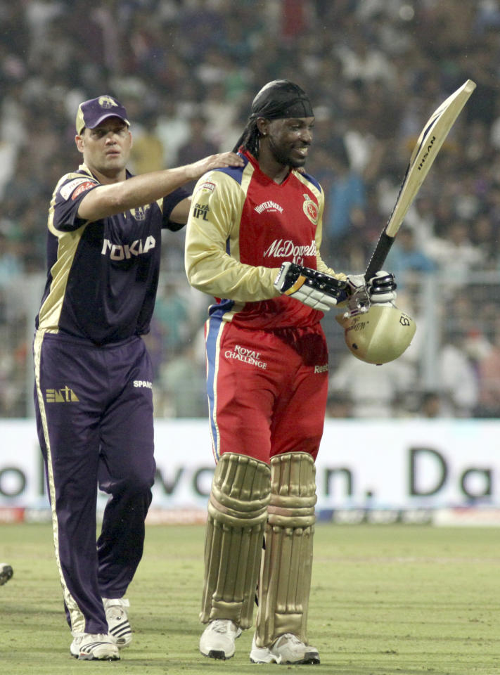 RESTRICTED TO EDITORIAL USE. MOBILE USE WITHIN NEWS PACKAGE Royal Challengers Bangalore batsman Chris Gayle (R) celebrates scoring a century (100 runs) as Kolkata Knight Riders cricketer Jacques Kallis gestures during the IPL Twenty20 match between Royal Challengers Bangalore and Kolkata Knight Riders at The Eden Garden Stadium in Kolkata on April 22, 2011.  AFP PHOTO/ STR (Photo credit should read STRDEL/AFP/Getty Images)