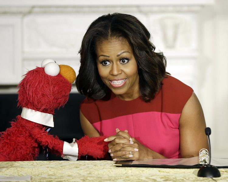 First lady Michelle Obama, center, with PBS Sesame Street's characters Elmo, left, attend an event to help promote fresh fruit and vegetable consumption to kids in an event in the State Dining Room of the White House in Washington, Wednesday, Oct. 30, 2013. Sesame Workshop and the Produce Marketing Association (PMA) joined in Partnership for a Healthier America (PHA) in announcing a 2-year agreement to making healthy choices by using the Sesame Street characters to help deliver the messages about fresh fruits and vegetables. (AP Photo/Pablo Martinez Monsivais)