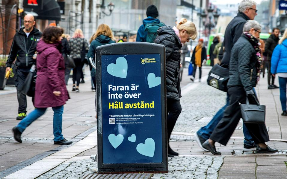 """Pedestrians in Uppsala walk past a bin that carries a sign saying """"the danger is not over - keep your distance"""" - TT News Agency/Claudio Bresciani via REUTERS"""