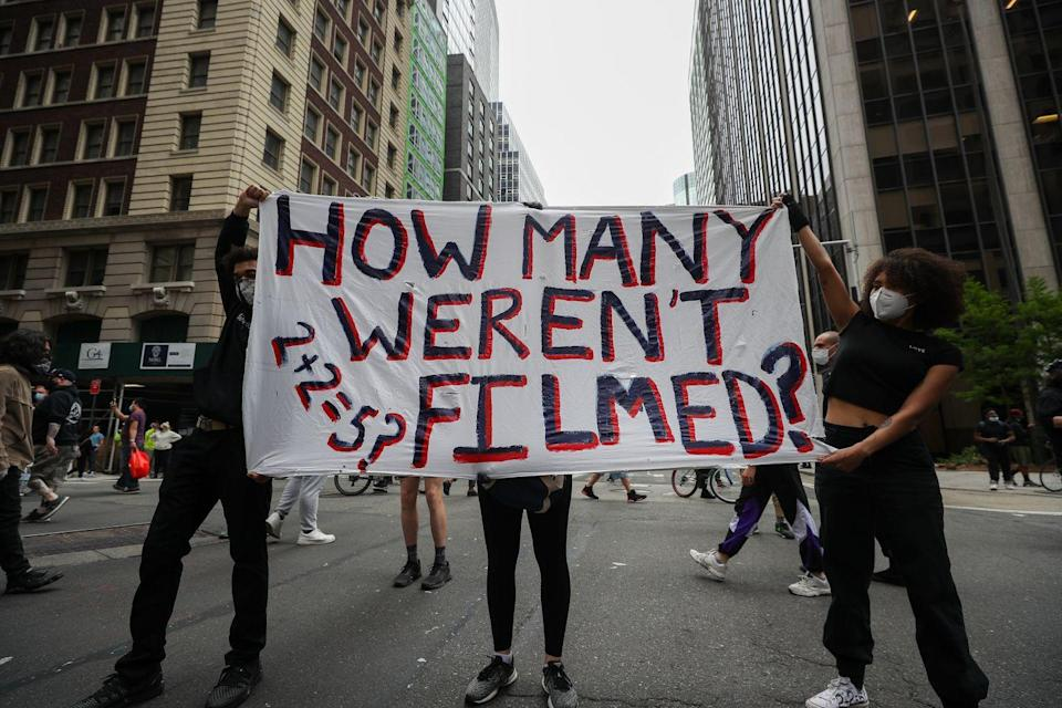 "<p>Several people hold a banner wondering ""How many [murders of BIPOC] weren't filmed?"" (2+2=5 has been used in literature and in the media to expose fake dogma.)</p>"