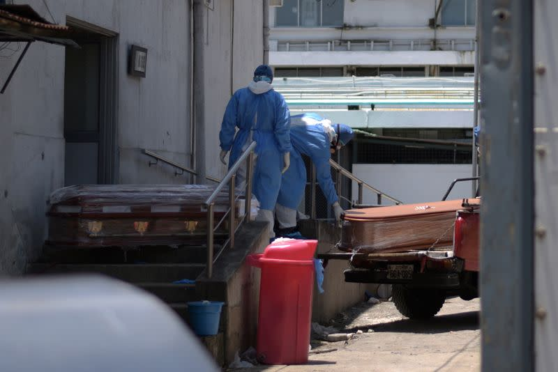Health workers wearing protective gear load coffins outside of Teodoro Maldonado Carbo Hospital amid the spread of the coronavirus disease (COVID-19), in Guayaquil