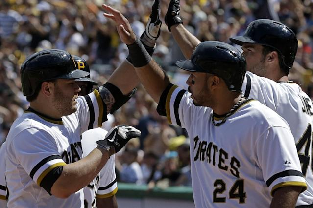 Pittsburgh Pirates' Russell Martin, left, is greeted by teammate Pedro Alvarez (24) after hitting a three-run home run off Colorado Rockies relief pitcher Manny Corpas (60) in fifth inning of a baseball game in Pittsburgh Sunday, Aug. 4, 2013. (AP Photo/Gene J. Puskar)