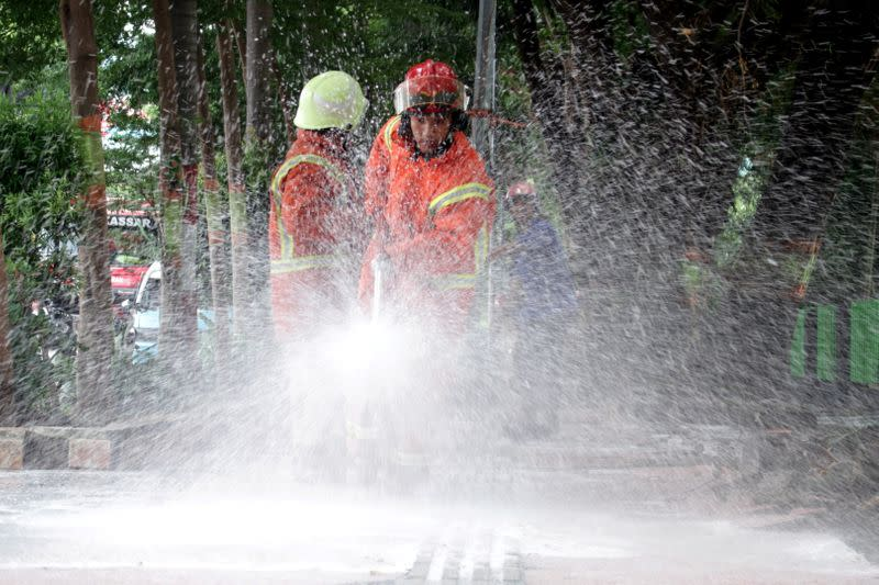 Firefighters spray disinfectant on the road, to prevent the spread of coronavirus disease (COVID-19) in Makassar