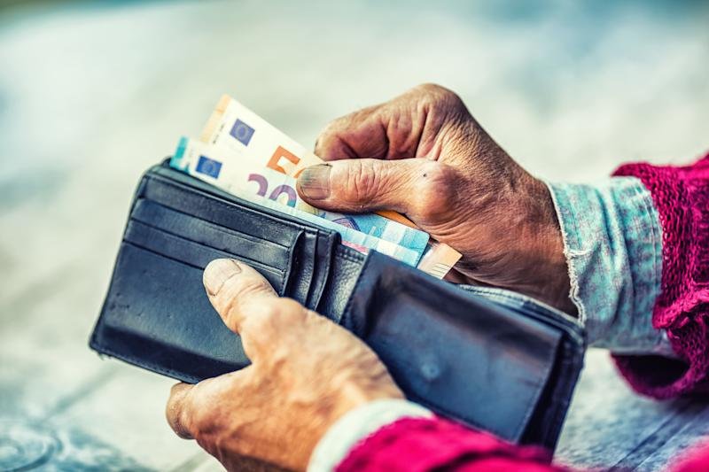 Pensioner man holding in hands wallet with money.