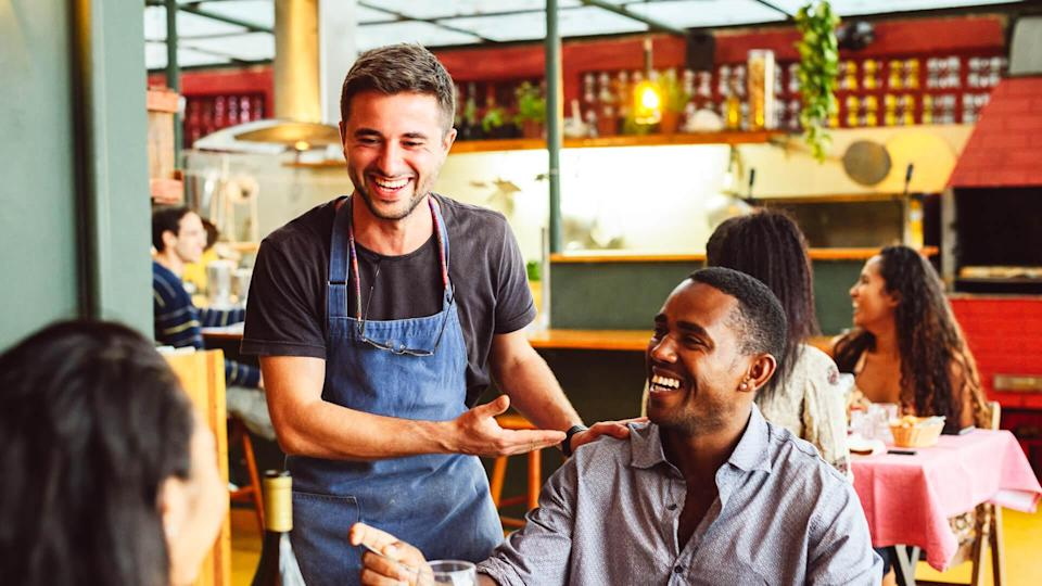 Couple sitting opposite each other in small restaurant, waiter standing and socialising, relaxed and friendly, customer service.