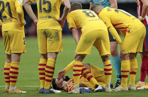 Barcelona's Gerard Pique, bottom, reacts after getting an injury during the Spanish La Liga soccer match between Atletico Madrid and FC Barcelona at the Wanda Metropolitano stadium in Madrid, Spain, Saturday, Nov. 21, 2020. (AP Photo/Bernat Armangue)