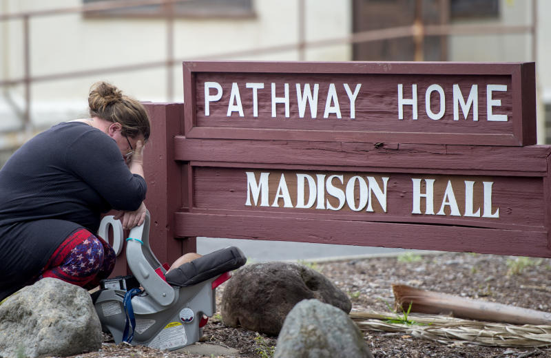 A woman, who declined to give her name, cries after placing flowers at a sign at the Veterans Home of California, the morning after a hostage situation in Yountville, Calif., on Saturday, March 10, 2018. A daylong siege at The Pathway Home ended Friday evening with the discovery of four bodies, including the gunman, identified as Albert Wong, a former Army rifleman who served a year in Afghanistan in 2011-2012. (AP Photo/Josh Edelson)