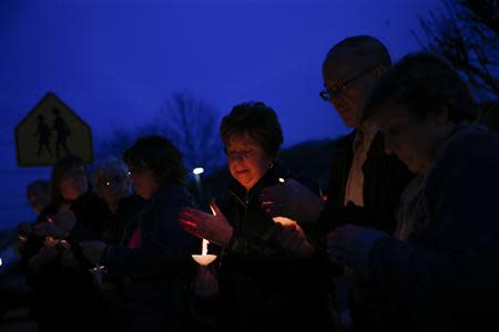 People hold candles during a prayer vigil for victims of the Franklin Regional High School stabbing rampage, at Calvary Lutheran Church in Murrysville, Pennsylvania April 9, 2014. REUTERS/Shannon Stapleton
