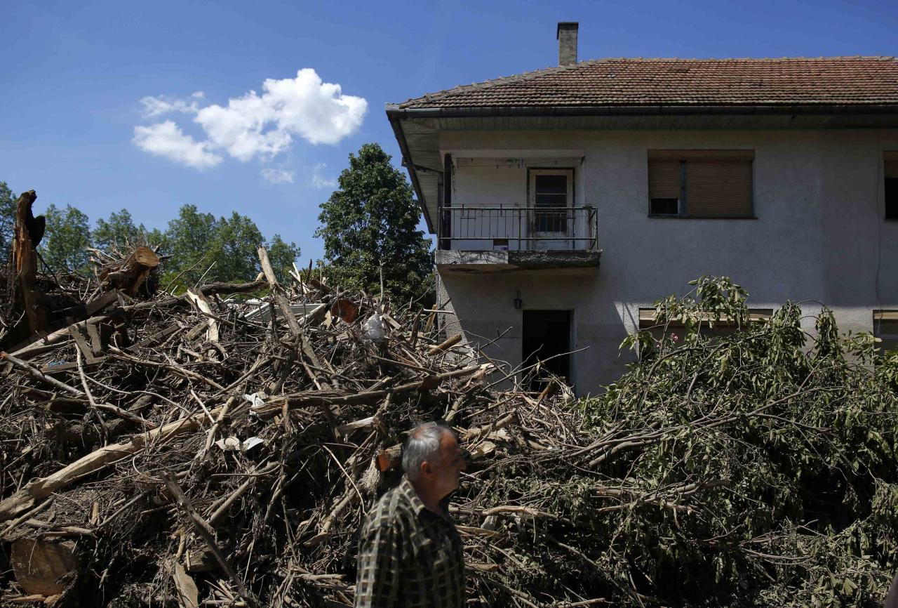A man walks near a flood-damaged house in Maglaj May 21, 2014. At least 40 people have died in Serbia, Bosnia and Croatia, after days of the heaviest rainfall since records began 120 years ago caused rivers to burst their banks and triggered hundreds of landslides. REUTERS/Dado Ruvic (BOSNIA AND HERZEGOVINA - Tags: DISASTER ENVIRONMENT)