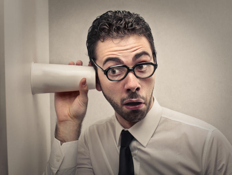 A man in a shirt and tie listens through a wall using a plastic cup.