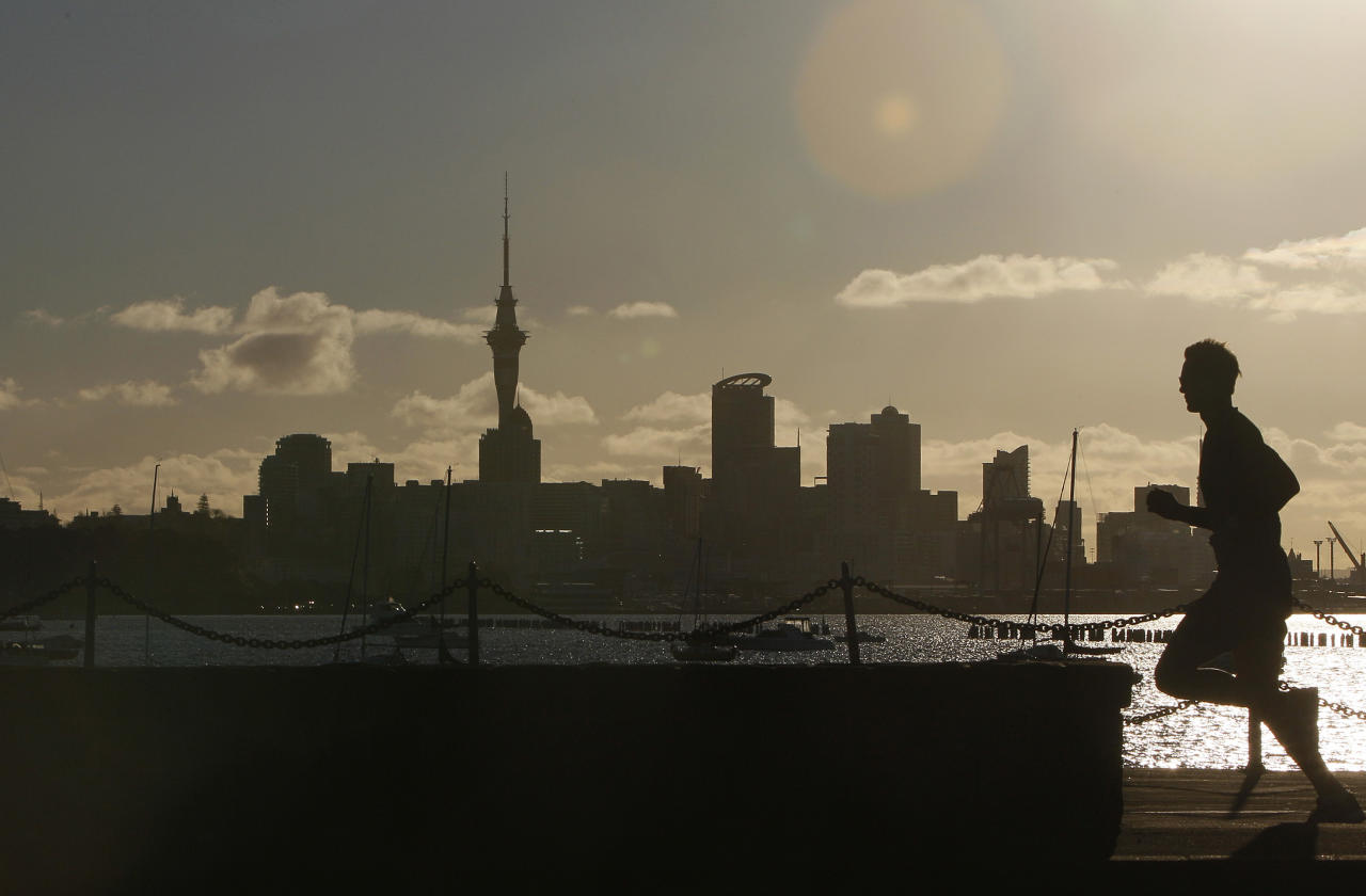 A jogger runs along the waterfront of Okahu Bay as the sun begins to set behind the main business district in Auckland, New Zealand, Monday, Sept. 26, 2011. The tower is 328 meters high (1,076 feet), the tallest man-made structure in New Zealand. (AP Photo/Alastair Grant)