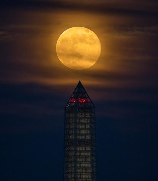 A supermoon climbed its way to the top of the Washington Monument, Sunday, June 23, 2013, in Washington. This year the supermoon is up to 13.5 percent larger and 30 percent brighter than a typical full moon is. This is a result of the moon reac