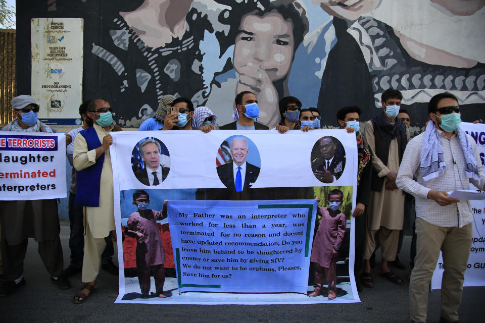 Former Afghan interpreters hold placards during a demonstrations against the US government, in front of the US Embassy in Kabul, Afghanistan, Friday, June 25, 2021. (AP Photo/Mariam Zuhaib)