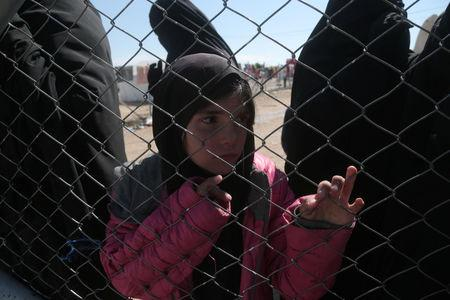 A girl looks through a chain linked fence at al-Hol displacement camp in Hasaka governorate, Syria March 8, 2019. REUTERS/Issam Abdallah