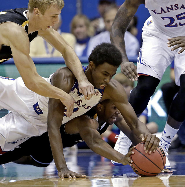Kansas guard Andrew Wiggins, center, battles Fort Hays State's Craig Nicholson, bottom, and Jake Stoppel, top, for a loose ball during the first half of an exhibition NCAA college basketball game Tuesday, Nov. 5, 2013, in Lawrence, Kan. (AP Photo/Charlie Riedel)