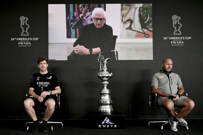 Italy's Luna Rossa skipper Max Sirena, right, and Team New Zealand skipper Peter Burling, left, attend a press conference with Prada CEO Patrizio Bertelli on video call, center, ahead of the start of America's Cup racing in Auckland, New Zealand, Tuesday, March 9, 2021. The best-of-13 race series is scheduled to begin on Wednesday. (Andrew Cornaga/Photosport via AP)