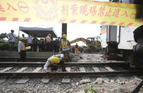 Workers inspect near the derailed train near Taroko Gorge in Hualien, Taiwan on Saturday, April 3, 2021. The train partially derailed in eastern Taiwan on Friday after colliding with an unmanned vehicle that had rolled down a hill, killing and injuring dozens. Workers began removing some of the train cars and repair work also has begun on the tracks including the tunnel where part of the eight-car train crashed. (AP Photo/Chiang Ying-ying)