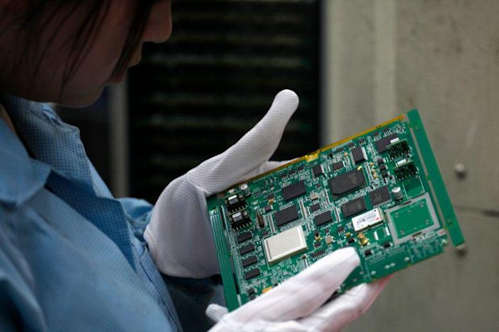 A ZTE employee checks a motherboard at a production line in a factory in Shenzhen, Guangdong province April 17,2012.China's ZTE Corp, which recently sold Iran's largest telecommunications firm a powerful surveillance system, later agreed to ship to Iran millions of dollars worth of embargoed U.S. computer equipment, documents show. REUTERS/Tyrone Siu