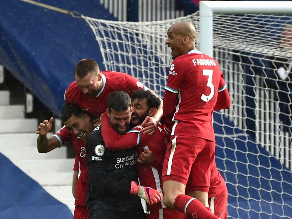 Liverpool players celebrate with Alisson after the goalkeeper's late winner against West Brom (Getty Images)