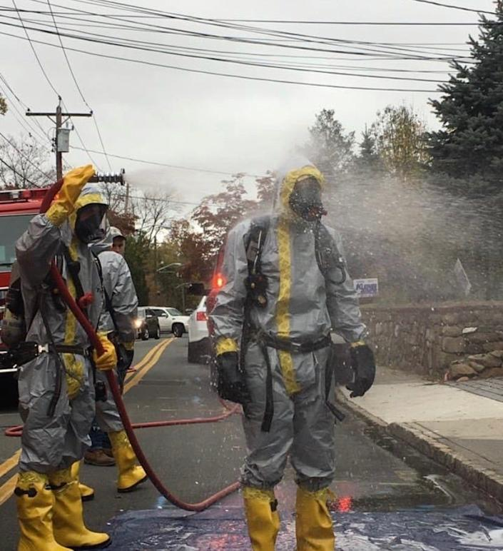 A Piermont, N.Y., first responder is decontaminated in July after an emergency call to protect against the COVID-19 virus.