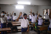Students attend a class at the Narinda Government High School as schools reopen after being closed for nearly 18 months due to the coronavirus pandemic in Dhaka, Bangladesh, Sunday, Sept.12, 2021. (AP Photo/Mahmud Hossain Opu)