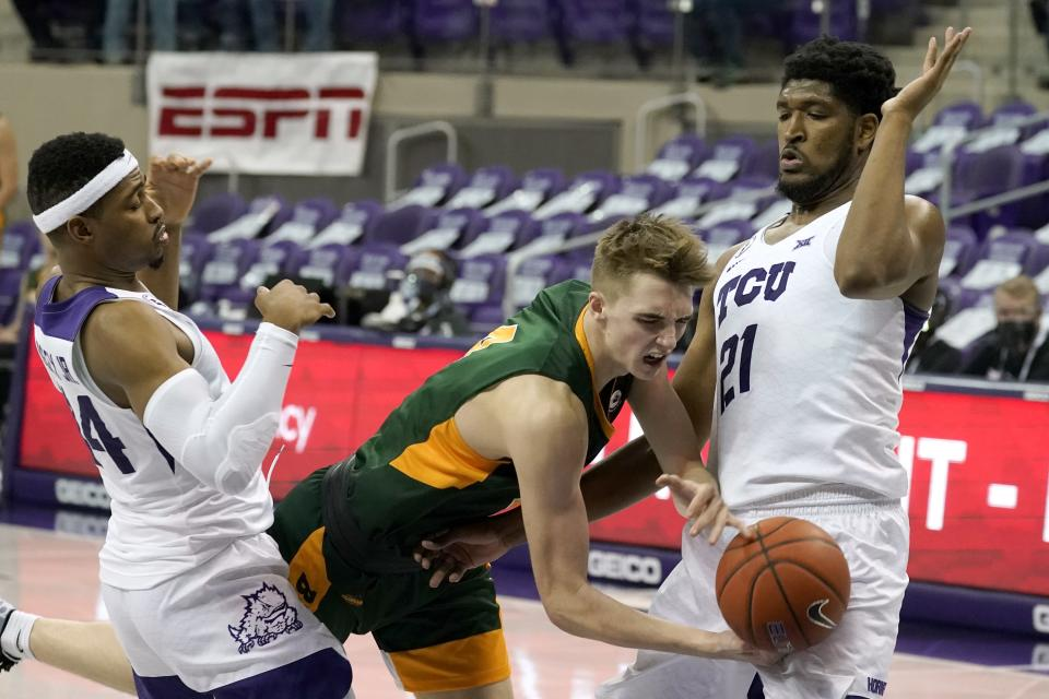 North Dakota State forward Grant Nelson, center, loses control of the ball on a drive to the basket as TCU forward Kevin Easley Jr., left, and Kevin Samuel, right, defends in the first half of an NCAA college basketball game in Fort Worth, Texas, Tuesday, Dec. 22, 2020. (AP Photo/Tony Gutierrez)