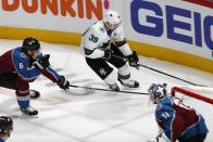 San Jose Sharks center Logan Couture, back right, drives to the net with the puck as Colorado Avalanche defenseman Erik Johnson, back left, and goaltender Philipp Grubauer defend during the first period of Game 3 of an NHL hockey second-round playoff series Tuesday, April 30, 2019, in Denver. (AP Photo/David Zalubowski)