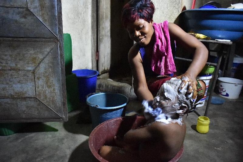 A woman washes her child with salted water, on August 25, 2014 in a suburb of Abidjan, relying on a rumor that was spread in the area claiming that salted water helps to fight against the Ebola virus (AFP Photo/Issouf Sanogo)