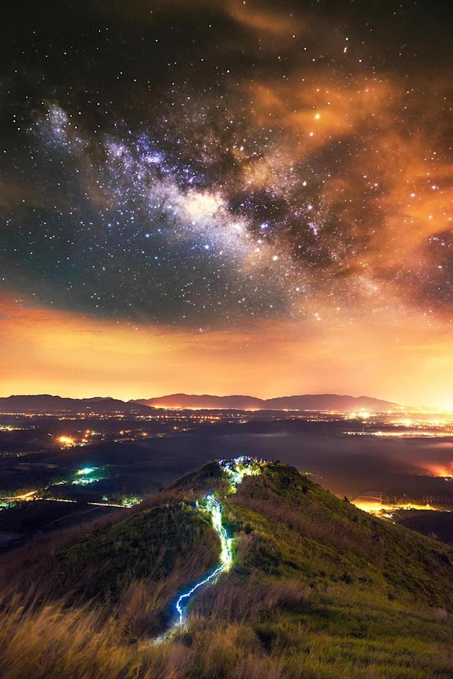 <p>The Milky Way over a lighted Broga Hill in Malaysia. (Photo: Grey Chow/Caters News) </p>