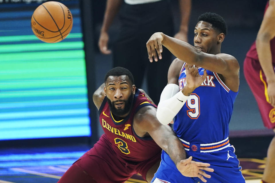 New York Knicks' RJ Barrett (9) passes the ball past Cleveland Cavaliers' Andre Drummond (3) during the first half of an NBA basketball game Friday, Jan. 15, 2021, in Cleveland. (AP Photo/Tony Dejak)