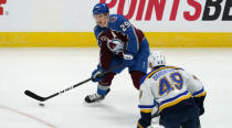 Colorado Avalanche center Nathan MacKinnon, back, looks to pass the puck as St. Louis Blues center Ivan Barbashev defends in the first period of an NHL hockey game Friday, Jan. 15, 2021, in Denver. (AP Photo/David Zalubowski)