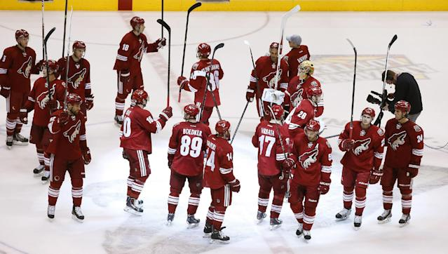 The Phoenix Coyotes players wave their sticks as they acknowledge the crowd after an NHL hockey game against the Dallas Stars on Sunday, April 13, 2014, in Glendale, Ariz. The Coyotes defeated the Stars 2-1. (AP Photo/Ross D. Franklin)