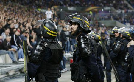 Police officers by the pitch after Lyon and Besiktas fans clashed in the stands