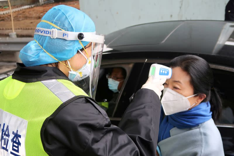 FILE PHOTO: A security officer in a protective mask checks the temperature of a passenger following the outbreak of a new coronavirus, at an expressway toll station on the eve of the Chinese Lunar New Year celebrations, in Xianning