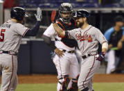 Miami Marlins' catcher Jorge Alfaro looks on as Atlanta Braves' Ender Inciarte, right, is congratulated by teammate Freddie Freeman after hitting a home run during the sixth inning of a baseball game, Sunday, June 13, 2021, in Miami. (AP Photo/Jim Rassol)