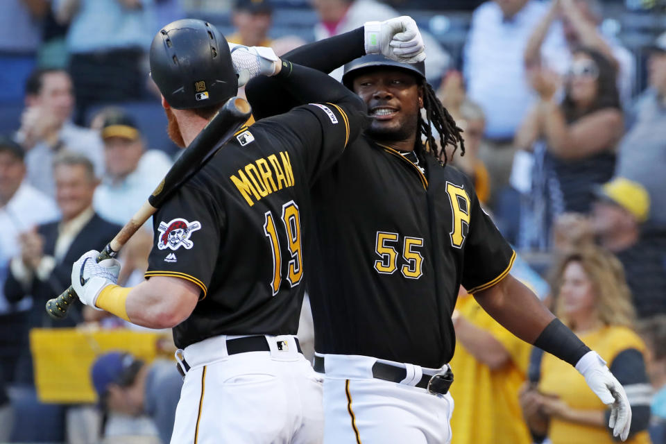 Pittsburgh Pirates' Josh Bell (55) celebrates with Colin Moran (19) as he returns to the dugout after hitting a three-run home run off Chicago Cubs starting pitcher Adbert Alzolay during the first inning of a baseball game in Pittsburgh, Monday, July 1, 2019. (AP Photo/Gene J. Puskar)