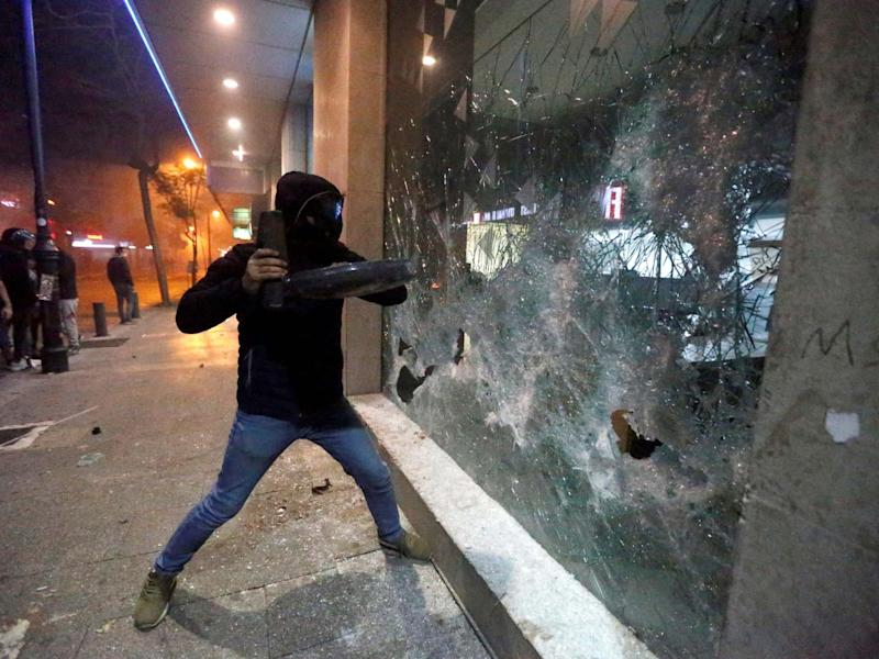 A protester smashes the window of a bank as demonstrations against the government continue in Beirut: Reuters