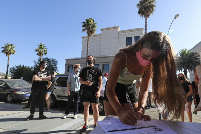 RIVERSIDE, CA - JULY 10: Hope Macias signs a petition drive organized by Augie's workers in front of the Riverside location asking people to sign a petition demanding that Augie's Coffee House to reopen. Riverside County chain recently shut down for what they say is coronavirus but whose former workers claim was in retaliation forming Augie's Union. Augie's Coffee House on Friday, July 10, 2020 in Riverside, CA. (Irfan Khan / Los Angeles Times)