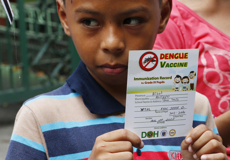 Eric John Vital, 12, holds his vaccination record as he joins other protesters at a rally outside the Department of Health to demand accountability to government officials involved in the controversial immunization of the anti-dengue vaccine Dengvaxia to more than 700,000 Filipino children Friday, Dec. 8, 2017 in Manila, Philippines. The controversial vaccine, manufactured by Sanofi Pasteur was put on hold by the Philippines last week after new study findings showed it posed risks of severe cases in people without previous infection. The controversy has prompted the Philippine Senate to conduct an investigation. (AP Photo/Bullit Marquez)