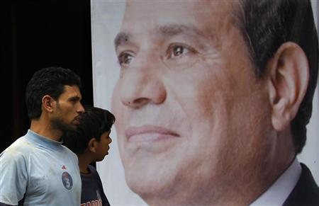 People walk past a poster of presidential candidate Abdel Fattah al-Sisi at one of his campaign headquarters in Cairo