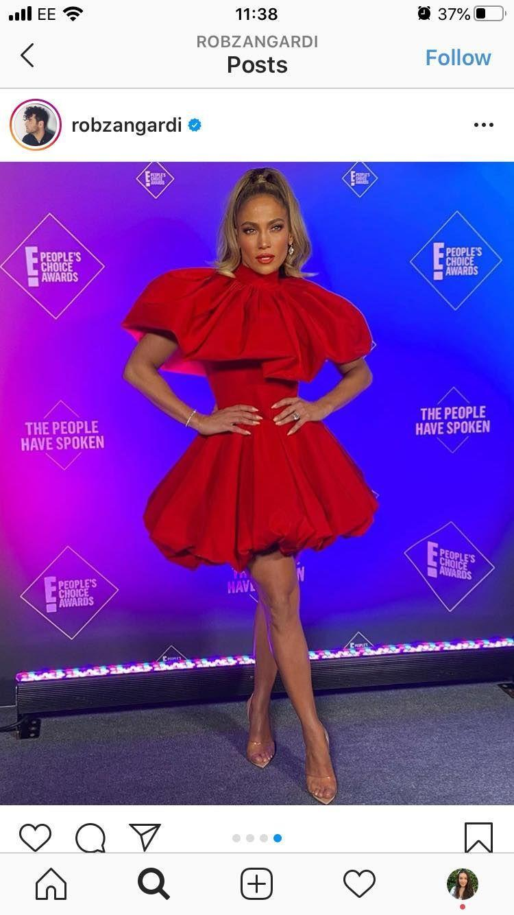 """<p>Jennifer Lopez wore a red puffball mini dress by Christian Siriano to receive her 'People's Icon' award at the People's Choice Awards. The 51 year-old paired the festive dress with clear heels and a high ponytail. </p><p><a href=""""https://www.net-a-porter.com/en-gb/shop/product/emilia-wickstead/bow-detailed-cutout-cloque-mini-dress/1275291"""" rel=""""nofollow noopener"""" target=""""_blank"""" data-ylk=""""slk:SHOP RED MINI DRESS NOW"""" class=""""link rapid-noclick-resp"""">SHOP RED MINI DRESS NOW</a></p>"""
