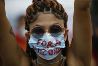 """A woman wearing a protective face mask marked with a message that reads in Portuguese: """"Get Out Bolsonaro"""" during a protest against Brazilian President Jair Bolsonaro's handling of the coronavirus pandemic and economic policies they say harm the interests of the poor and working class, in Rio de Janeiro, Brazil, Saturday, June 19, 2021. Brazil is approaching an official COVID-19 death toll of 500,000 — second-highest in the world. (AP Photo/Bruna Prado)"""