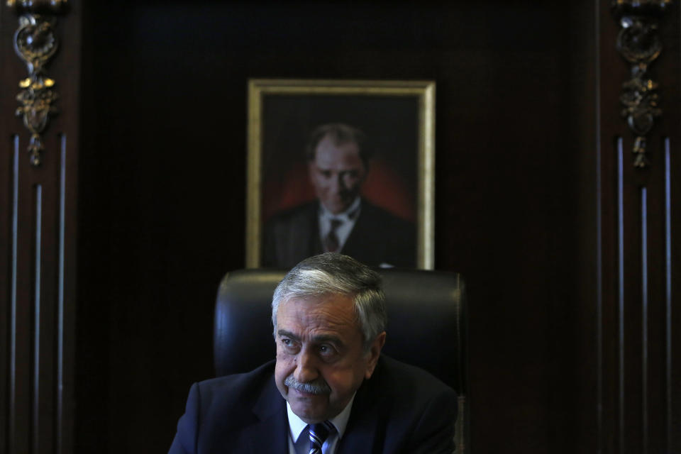 FILE - In this Monday, April 4, 2016 file photo, Turkish Cypriot leader Mustafa Akinci sits in his office in front of a portrait of the Turkish Republic founder Kemal Ataturk, during an interview for the Associated Press in the Turkish breakaway north part of the divided capital Nicosia in this ethnically Mediterranean island of Cyprus. Turkish Cypriots will vote Sunday Oct. 11, 2020 to choose a leader who will explore, with rival Greek Cypriots, whether there's enough common ground left for a deal to end the island's decades of ethnic division. (AP Photo/Petros Karadjias, File)