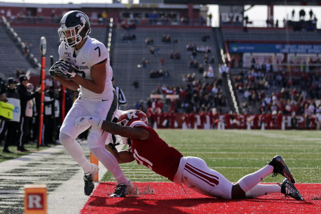 Michigan State wide receiver Cody White (7) scores a touchdown in front of Rutgers defensive back Tim Barrow (21) during the first half of an NCAA college football game Saturday, Nov. 23, 2019, in Piscataway, N.J. (AP Photo/Adam Hunger)