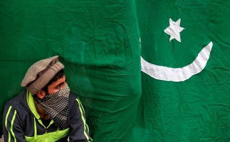 A masked protester sits next to a flag of Pakistan during an anti-Indian protest in Srinagar, November 25, 2016. REUTERS/Danish Ismail