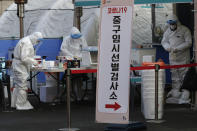 Medical workers wearing protective gears prepare to take sample at a coronavirus testing site in Seoul, South Korea, Thursday, Dec. 24, 2020. (AP Photo/Lee Jin-man)