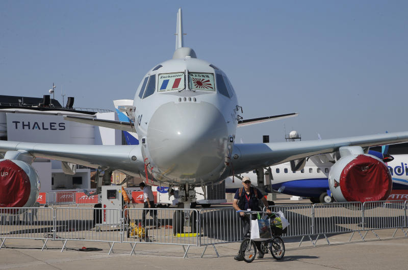 A man walks past with his bicycle a Japan maritime self-defense forces P-1 submarine-hunting aircraft, at Paris Air Show, on the eve of its opening, in Le Bourget, east of Paris, France, Sunday, June 18, 2017. While Airbus and Boeing will again hog the spotlight at the Paris Air Show with their battle for ever-larger slices of the lucrative pie in the sky, a lot of the really interesting stuff will be going on elsewhere at next week's massive biennial aviation and defense industry gathering. (AP Photo/Michel Euler)