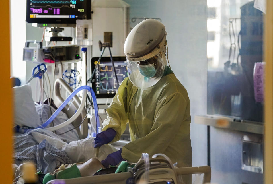 FILE - In this Wednesday, Jan. 13, 2021, file photo, a health care worker tends to a COVID-19 patient in the intensive care unit at Santa Clara Valley Medical Center during the coronavirus pandemic in San Jose, Calif. The coronavirus death toll in California surpassed 50,000 on Wednesday, Feb. 24, 2021, marking about one-tenth of the U.S. total from the pandemic. (AP Photo/Jeff Chiu, File)