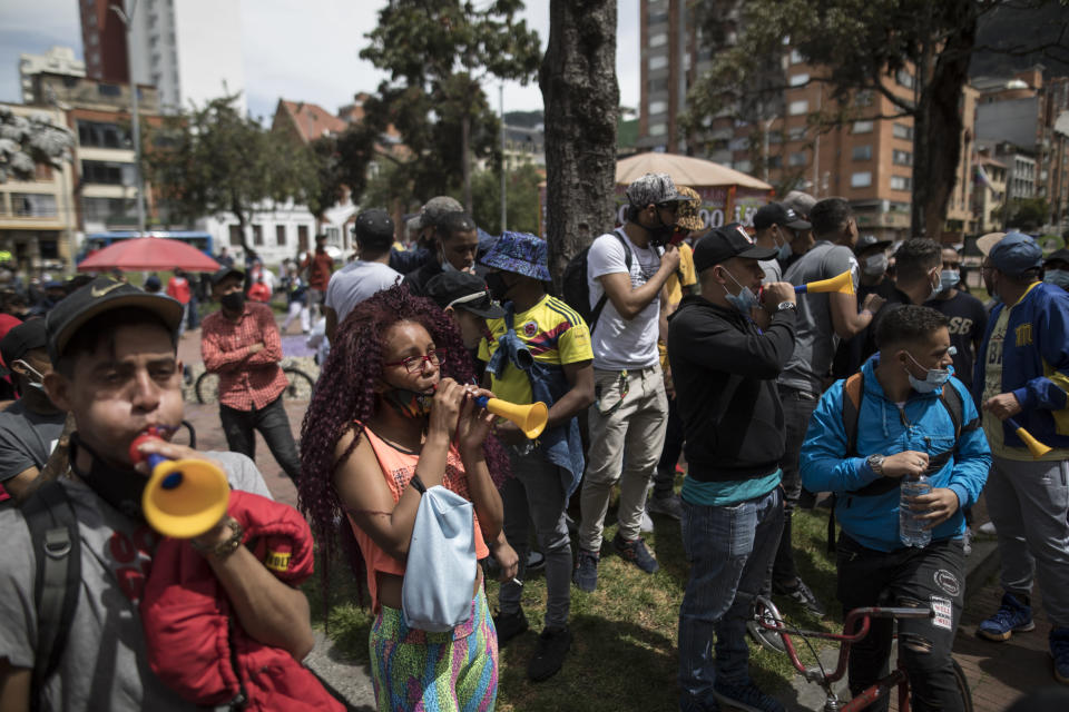 Protesters march toward the residence of Bogota Mayor Claudia López to demand the lifting of the city-wide curfew and the reopening of business amid the COVID-19 pandemic in Bogota, Colombia, Wednesday, Jan. 20, 2021. (AP Photo/Ivan Valencia)